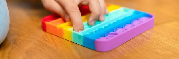 Антистресс сенсорные игрушки pop it в детских руках маленькая девочка играет с игрушкой дома