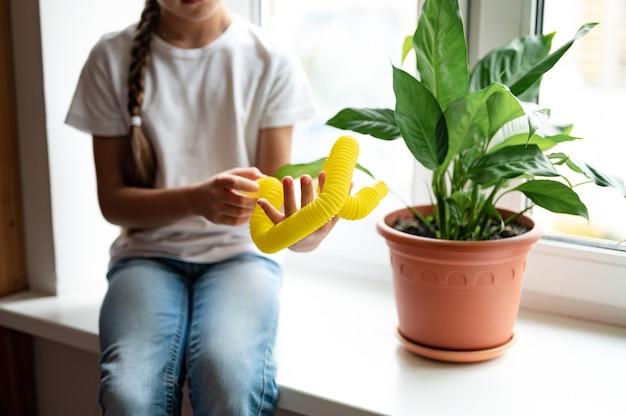 Антистрессовая сенсорная пластиковая игрушка поп-трубка в руках ребенка. маленькая счастливая девочка играет с игрушкой непоседа poptube дома. дети держат и играют в поп-трубку желтого цвета, тренд 2021 года