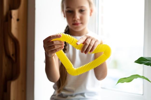 아이의 손에 안티 스트레스 감각 팝 튜브 플라스틱 장난감. 행복한 어린 소녀가 집에서 팝튜브 안절부절 장난감을 가지고 놀고 있습니다. 팝 튜브 노란색을 들고 노는 어린이, 추세 2021년
