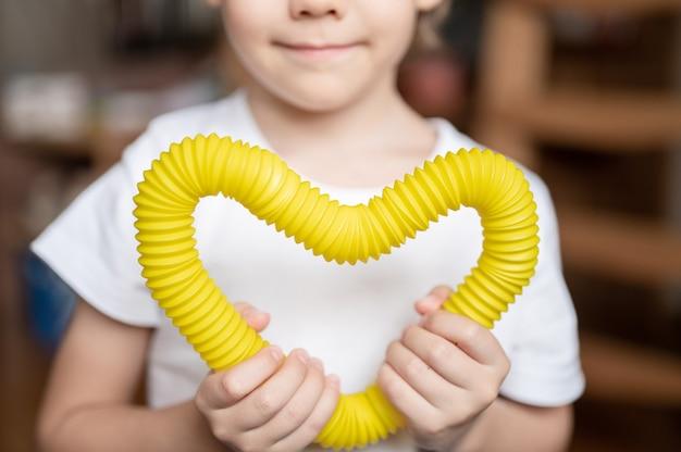 아이의 손에 안티 스트레스 감각 팝 튜브 플라스틱 장난감. 작은 행복한 소년은 집에서 팝튜브 안절부절 장난감을 가지고 노는다. 2021년 트렌드 팝 튜브 여러 색상을 들고 연주하는 어린이