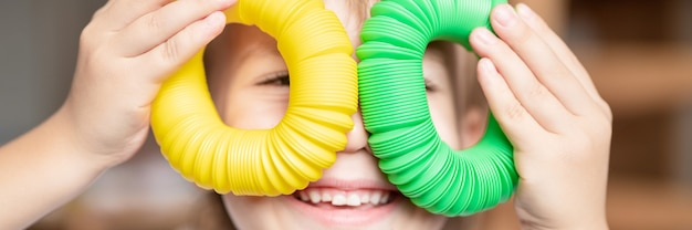 아이의 손에 안티 스트레스 감각 팝 튜브 플라스틱 장난감. 작은 행복한 소년은 집에서 팝튜브 안절부절 장난감을 가지고 노는다. 팝 튜브 노란색과 녹색을 들고 노는 아이들. 배너