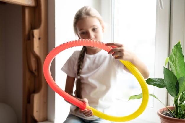 아이의 손에 안티 스트레스 감각 팝 튜브 플라스틱 장난감. 행복한 어린 소녀가 집에서 팝튜브 안절부절 장난감을 가지고 놀고 있습니다. 팝 튜브 노란색과 빨간색을 잡고 노는 어린이, 추세 2021년