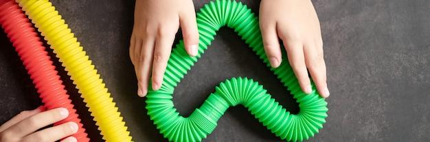 아이들의 손에 있는 안티 스트레스 감각 팝 튜브 장난감. 작은 행복한 아이들은 검은 탁자에서 팝튜브 장난감을 가지고 노는다. 여러 가지 빛깔의 밝은 색상의 팝 튜브를 들고 연주하는 유아들. 배너
