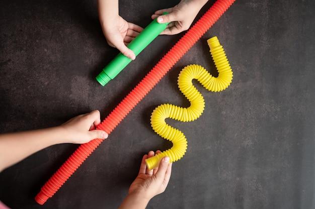 아이들의 손에 있는 안티 스트레스 감각 팝 튜브 장난감. 작은 행복한 아이들이 검은 탁자에서 팝튜브 장난감을 가지고 노는 것입니다. 팝 튜브 여러 가지 빛깔의 밝은 색상을 잡고 연주하는 유아, 추세 2021 년