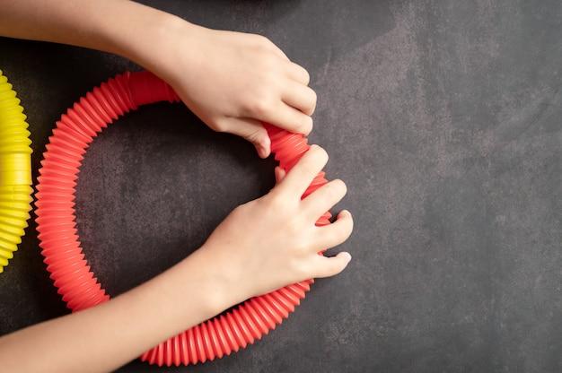 아이들의 손에 안티 스트레스 감각 팝 튜브 장난감. 작은 행복한 아이들은 검은 탁자에서 팝튜브 장난감을 가지고 노는다. 팝 튜브 빨간색과 노란색 밝은 색상, 추세 2021 년을 들고 연주하는 유아