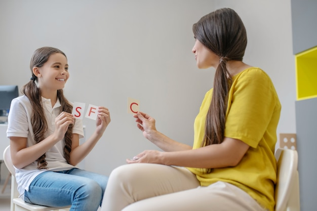 스트레스 해소 요법. 의사 소통 학교 나이 소녀와 여자 심리학자가 손에 편지를 들고 카드를 보여주는 미소