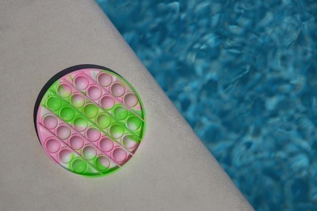 アンチストレスのおもちゃがそれをポップし、プールの側面にシンプルなディンプル、コピースペース。そわそわする子供のためのトレンディな夏の娯楽、細かい運動能力の発達のための感覚玩具、ストレス解消のコンセプト。
