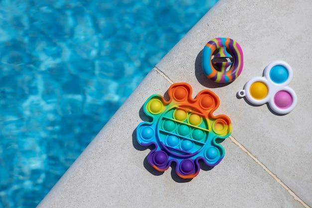 스트레스 방지 장난감이 튀어나오고, 단순한 보조개, 수영장 옆에 있는 스내퍼즈, 복사 공간. 안절부절 못하는 아이들을 위한 최신 유행의 엔터테인먼트, 미세 운동 기술 개발을 위한 감각 장난감, 스트레스 해소.