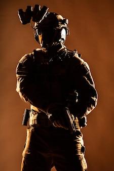 테러리스트 분대원, 마스크를 쓴 육군 엘리트 군인, 헬멧에 야간 투시 장치와 전술 라디오 헤드셋, 무장 서비스 권총이 행동 준비, 낮은 키 스튜디오 촬영