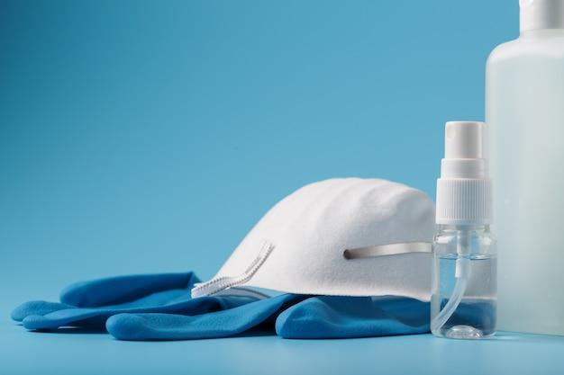 青色の背景、マスク、ゴム手袋、手の消毒剤ボトル、防腐剤ゲルのウイルス対策キット。