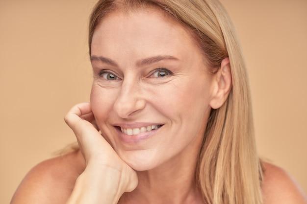 Антивозрастные процедуры крупным планом портрет привлекательной счастливой женщины средних лет, касающейся ее лица и
