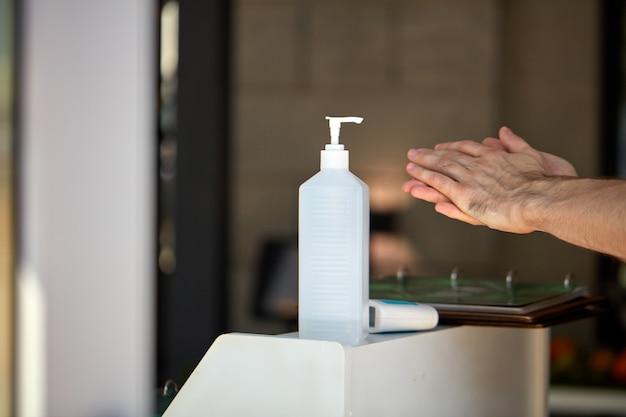 発生コロナウイルスの拡散を防ぐために手を洗う人々のための建物の入り口にある抗菌手指消毒剤ボトル