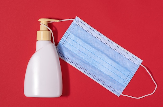 Антибактериальное мыло и медицинская маска для профилактики коронавируса на красном фоне, вид сверху
