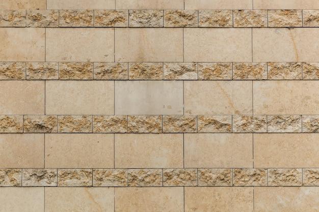 アンティークタイル。ヴィンテージベージュのタイルで壁のクローズアップ。