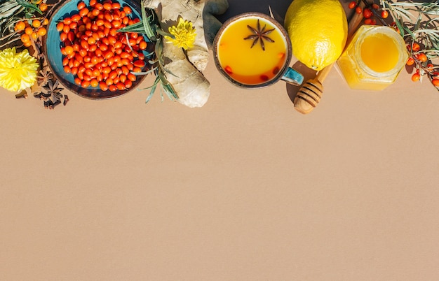 シーバックソーンティーハニーレモンと生姜のアンチコールドセット、ライトブラウンの背景の抗酸化物質