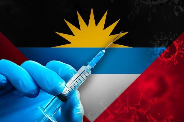 앤티가 바부다 코비드19 예방 접종 캠페인 파란색 고무 장갑을 끼고 깃발에 주사기를 들고 있습니다