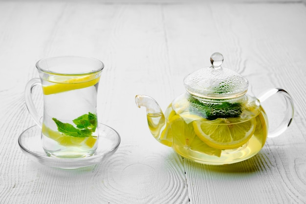 Antioxidant hot drink with lemon and mint in transparent tea pot and glass