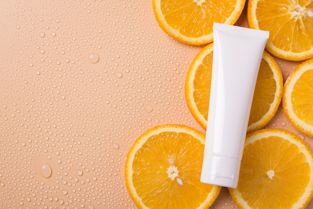 Antioxidant lifestyle wellness branding concept. top above flatlay flat lay overhead close up view photo of blank cream tube lying on slices of orange fruit isolated beige background copy empty space