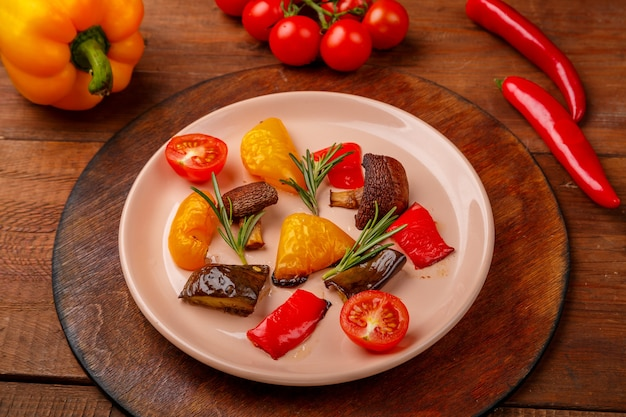 Антипаста на тарелке на подставке на деревянном столе рядом со свежими овощами. горизонтальное фото