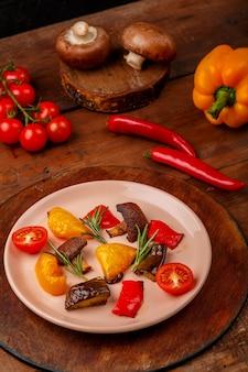 Антипаста на тарелке на подставке на деревянном столе рядом с овощами. вертикальное фото