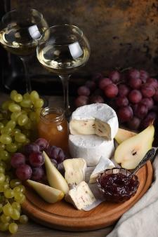 前菜。ブドウ、スライスした洋ナシ、コンフィチュールを添えたチーズカマンベールは、ワインの素晴らしい前菜です。