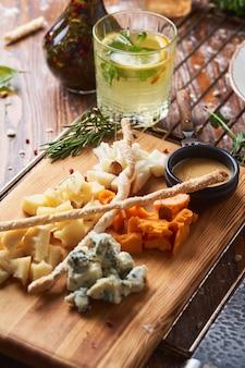 Закуски, разные виды сыра на деревянной доске с медом
