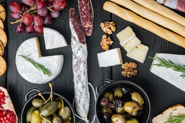 Antipasti platter with fresh cheese, bread and olives, on black wooden table, top view