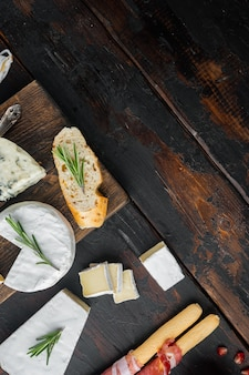 Antipasti platter with fresh cheese, bread and olives, on dark wooden background, flat lay  with copy space for text