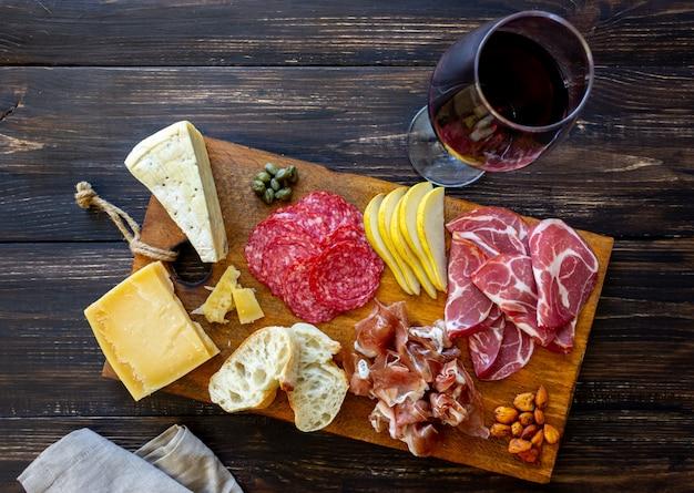 Винная закуска. прошутто, пармская ветчина, салями, миндаль, оливки, багет, голубой сыр, пармезан. antipasti.