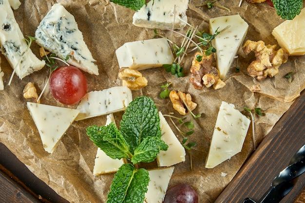 Антипасто - сырная тарелка. разные, домашние сыры на керамической тарелке - бри, камамбер, голландский с медом и орехами. винная закуска. вид сверху еды