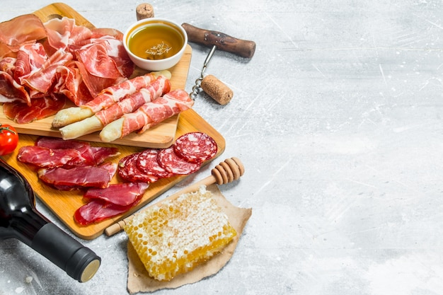 Antipasto background.assortment of meat snacks with red wine. on a rustic background.
