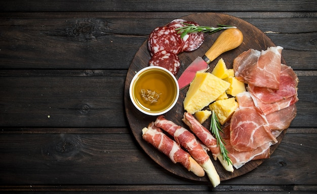 Antipasto background.board with traditional italian snacks. on a wooden background.