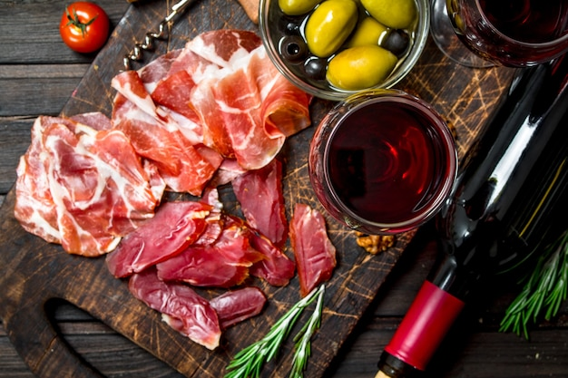 전채 배경. 레드 와인과 다른 고기 간식. 나무 배경.