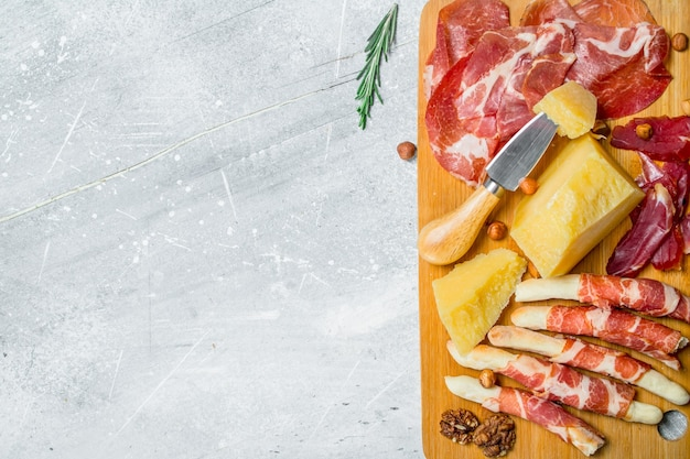 Antipasto background.meat and cheese snacks on the board. on a rustic background.