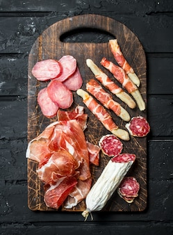 Antipasto background. variety of italian snacks. on a rustic background.