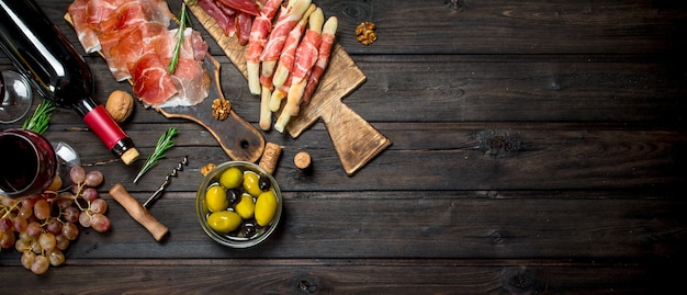 Antipasto background.various meat appetizer with olives, jamon and red wine.