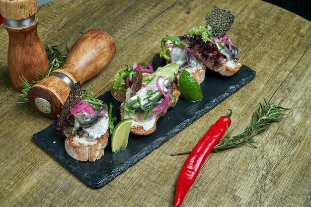 アンティパスト-ブルスケッタと塩漬けのスプラットまたはニシンのフェタチーズ、石のトレイにあるフランスのバゲット。メインコースの前に素晴らしい前菜