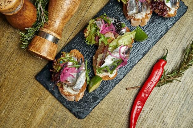 アンティパスト-ブルスケッタと塩漬けのスプラットまたはニシンのフェタチーズ、石のトレイにあるフランスのバゲット。トップビュー、コピースペース付きフラットレイアウト