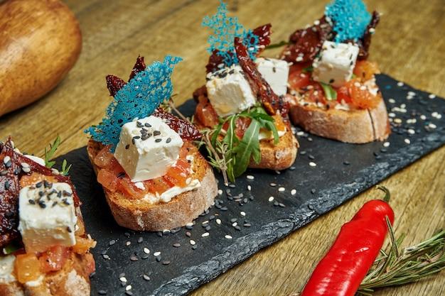 アンティパスト-天日干しトマトのブルスケッタ、石のトレイにあるフランスのバゲットにフェタチーズ。メインコースの前に素晴らしい前菜。クローズアップ、セレクティブフォーカス