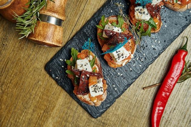 アンティパスト-天日干しトマトのブルスケッタ、石のトレイにあるフランスのバゲットにフェタチーズ。メインコースの前に素晴らしい前菜。トップビュー、コピースペース付きフラットレイアウト
