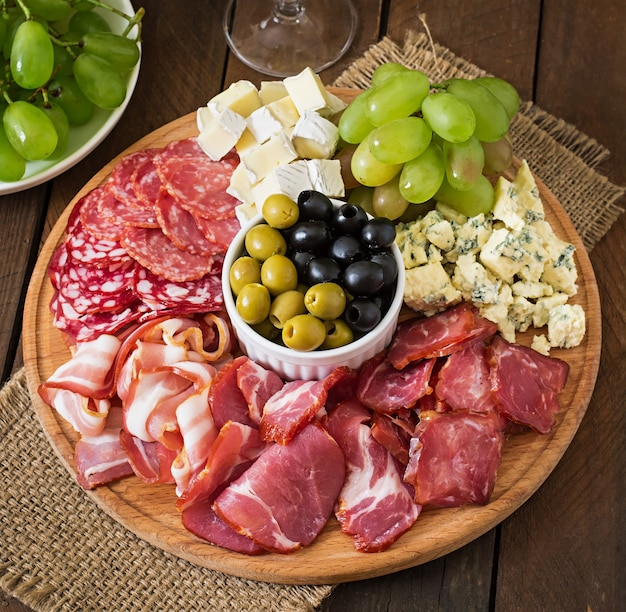 Antipasto catering platter with bacon, jerky, salami, cheese and grapes on a wooden table