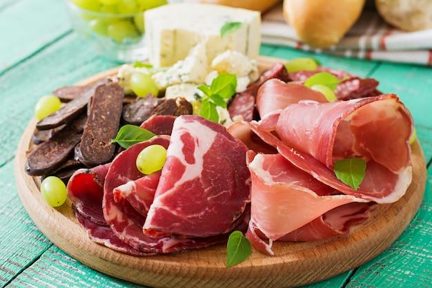 Антипасто блюдо с беконом, вяленым мясом, колбасой, голубым сыром и виноградом