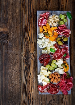 Antipasto catering platter with bacon, jerky, sausage, blue cheese and grapes on a wooden table. top view