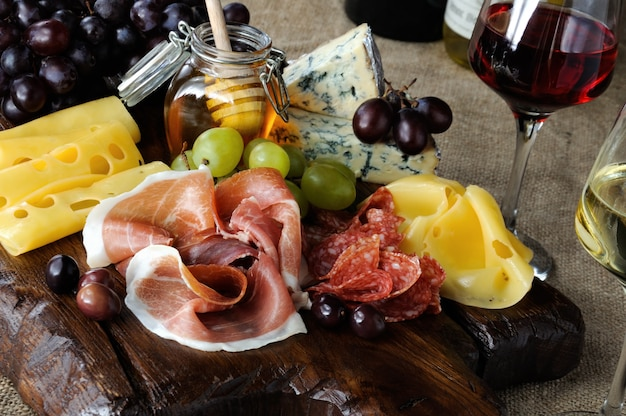 Antipasto catering platter with jerky bacon,  prosciutto, salami, cheese and grapes on a wooden background