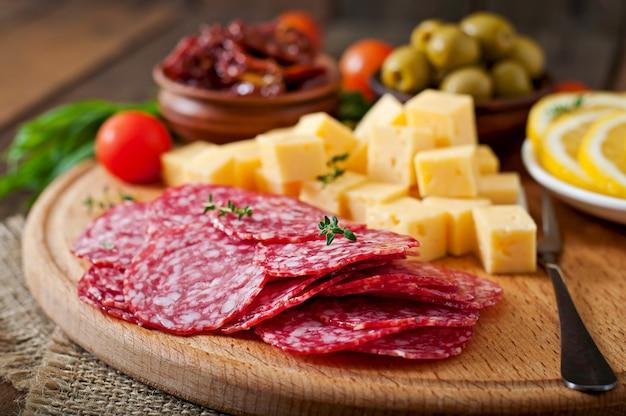 Антипасто блюдо с салями и сыром на деревянном
