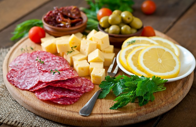 Antipasto catering platter with salami and cheese on wood