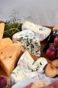 전채. 브리 치즈, 카망베르, 블루 치즈, 라다 머, 무스카트 포도 덩굴, 과일과 함께 가벼운 애피타이저 조각을 곁들인 요리.