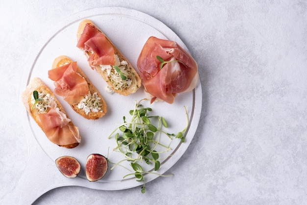 Antipasto of ham, ricotta and microgreens, crostini with prosciutto on a white background, close-up.