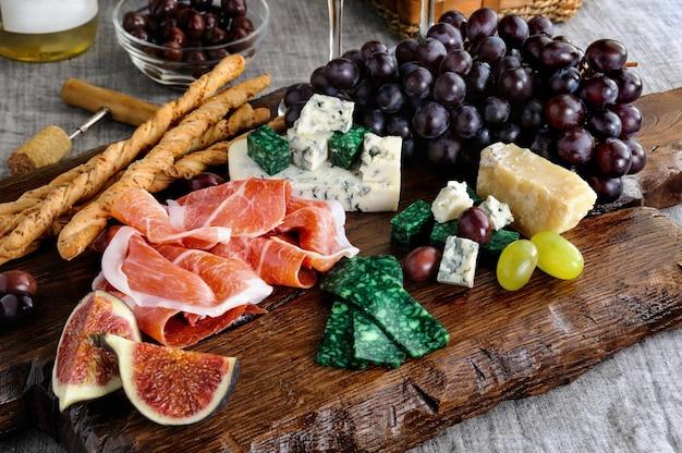 와인이 있는 테이블에 치즈 포도와 무화과의 프로슈토가 있는 나무 판자에 안티파스토