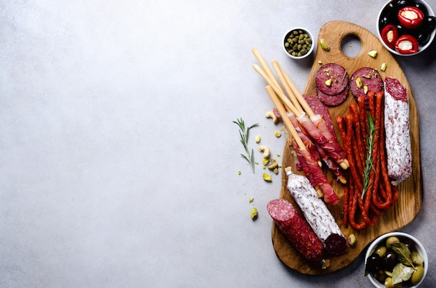 Antipasto plate with meat, olives, grissini bread sticks on grey concrete. top view, copy space, flat lay